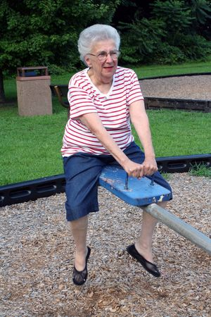 totter: Senior citizen woman on playground seesaw.
