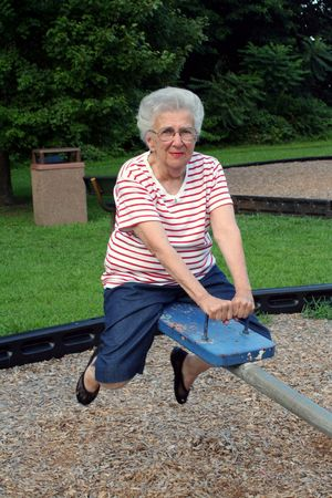 Senior citizen woman on playground seesaw.
