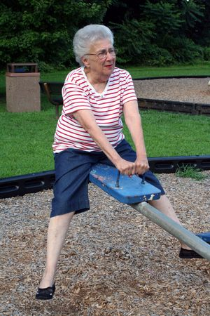 Senior citizen woman on playground seesaw.