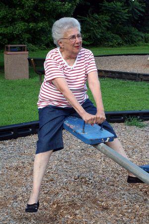 romp: Senior citizen woman on playground seesaw.