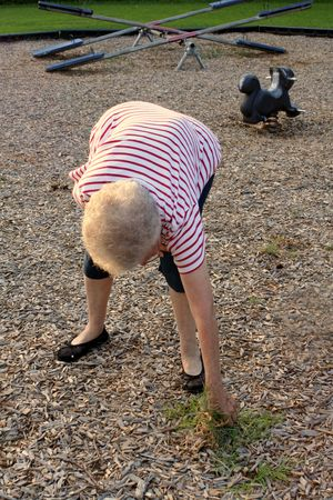 Senior citizen woman clearing weeds from a public playground. Stock Photo - 592047