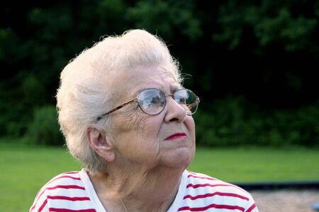 bifocals: Portrait of senior citizen woman at a park, looking up and away.