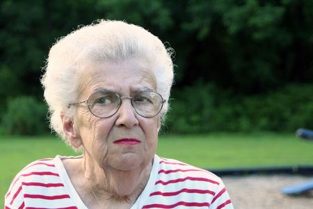Portrait of suspicious looking senior citizen woman at a playground. photo
