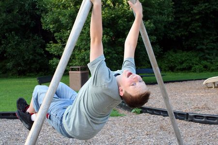 relive: Teenage boy hanging from playground apparatus. Stock Photo