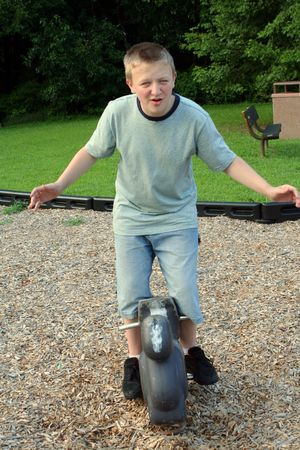 clowning: Teenage boy clowning on a childs ride at a playground. Stock Photo