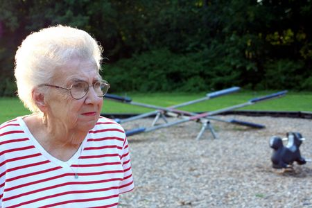 contradict: Portrait of pensive senior citizen woman at a playground.