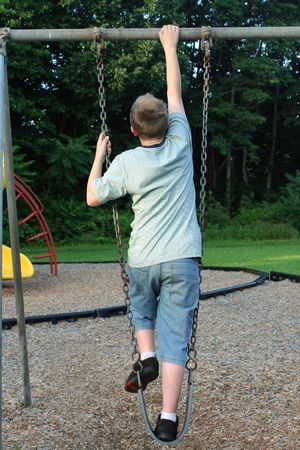 relive: Teenage boy climbing on a playground swing. Stock Photo