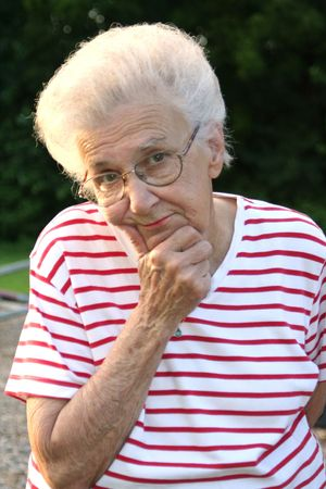 Senior citizen woman in thinking pose.