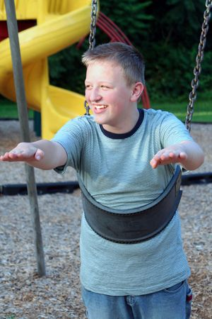 clowning: Teenage boy clowning in a playground childs swing.