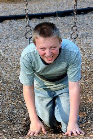 relive: Teenage boy in playground childs swing