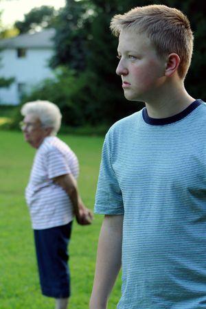 Outdoor portrait of serious teenage boy with grandmother in background. Standard-Bild