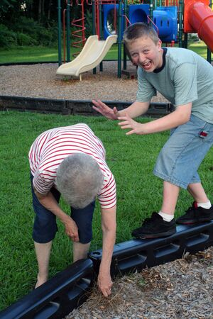 horseplay: Teenage boy engaged in horseplay with grandmother at playground. Stock Photo