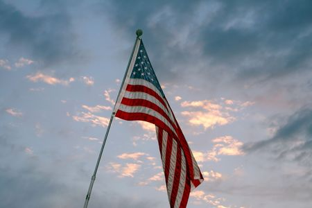 signify: American flag in wind against blue sky and clouds.