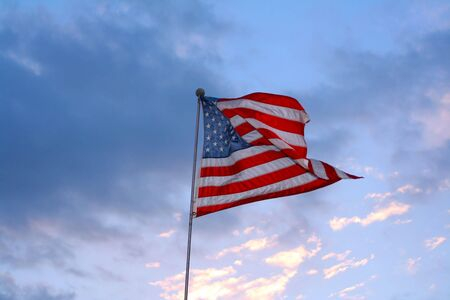 embody: American flag in wind against blue sky and clouds.