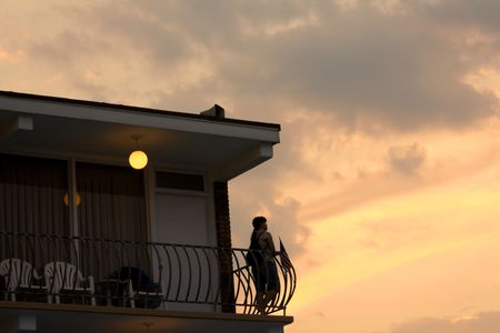 Woman standing on a motel balcony watching the sunset. Imagens