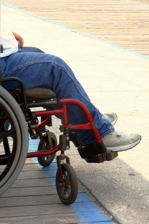Man in wheelchair on a boardwalk.  Legs showing only. Stock Photo