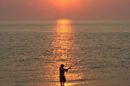 afflux: Silhouette d'un homme de surf de p�che au coucher du soleil.