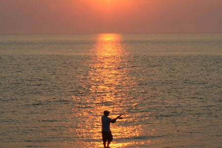 Silhouette of man surf fishing at sunset.