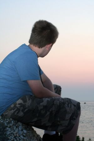 relive: Pensive teenage boy looking out at the ocean at sunset.