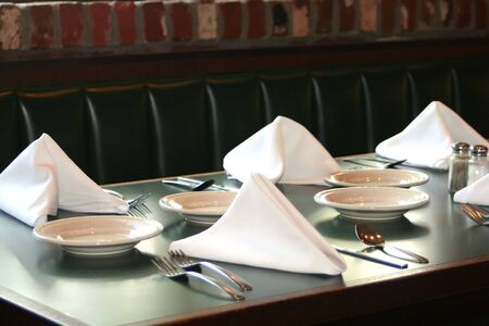 Restaurant table set with plates, utensils and linen napkins.
