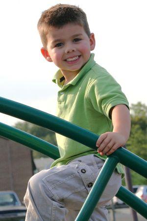 Smiling boy climbing on playground equipment.