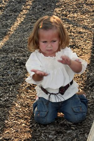 eradicate: Little girl on a playground brushing dirt from her hands in annoyance.