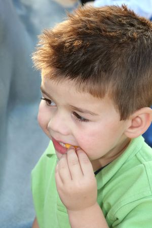 appease: Young boy having a snack outdoors. Stock Photo