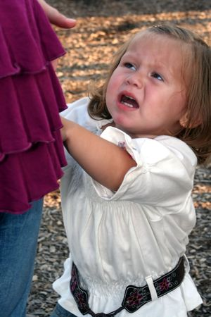 Little girl crying, holding onto and looking up at her mother. Stock Photo