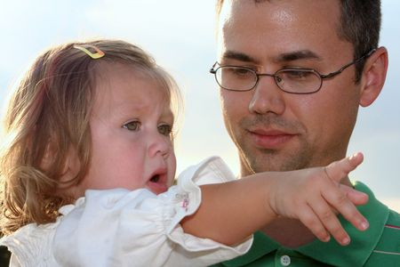 disapprove: Little girl pointing and explaining to her father. Stock Photo