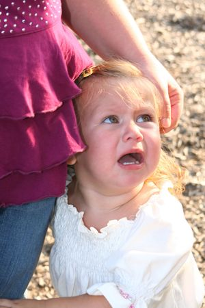 soothe: Little girl crying at her mothers side.