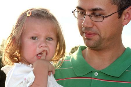 Sad little girl with unsure expression being held by her father. Stock Photo