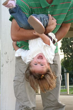Little girl laughing as her father turns her upside down. Imagens