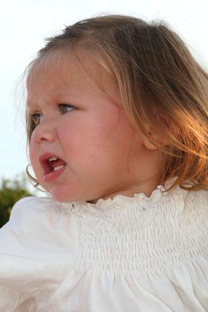 quandary: Outdoor portrait of an upset little girl.