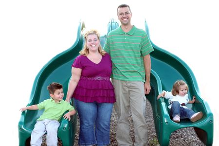 Family posed on a playground at sliding boards. Stock Photo - 684691