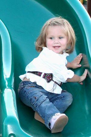 romp: Smiling little girl sliding on a playground sliding board.
