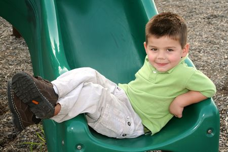 Young boy lounging at the bottom of a sliding board.