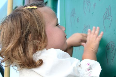 fingerspelling: Young girl imitating sign language printed on a wall at a playground. Stock Photo