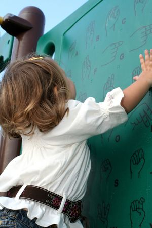 fingerspelling: Little girl studying sign language gestures at a playground.