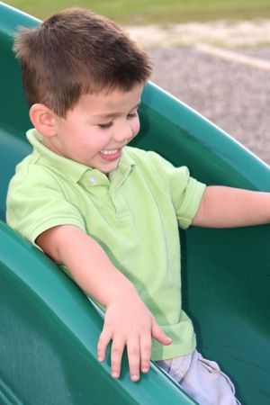 ebullient: Young smiling boy sliding down a sliding board.