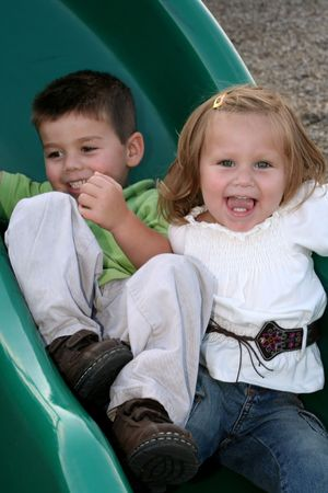 impish: Brother and sister sliding down a sliding board together. Stock Photo