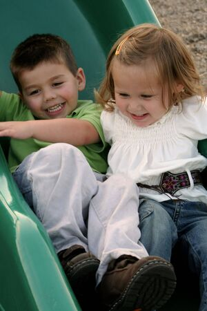 Brother and sister sliding down a sliding board together. Imagens