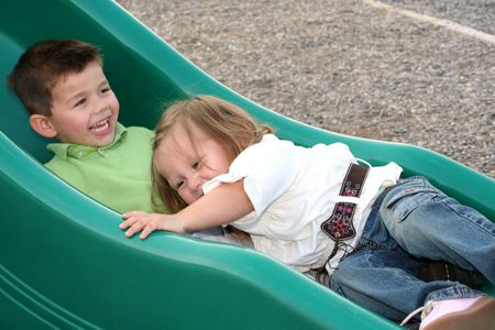 kinship: Brother and sister sliding down a sliding board together. Stock Photo