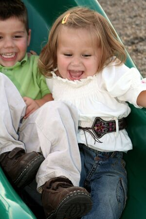ebullient: Brother and sister sliding down a sliding board together. Stock Photo