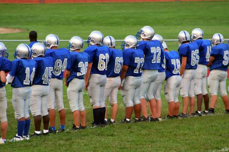 High school football team lined up on field.