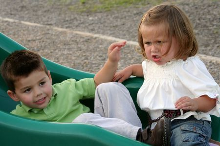 Angry little girl being ignored by her older brother as they sit at the bottom of a playground sliding board. Stock Photo