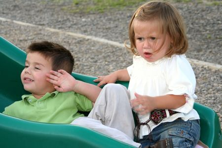 huffy: Angry little girl being ignored by her older brother as they sit at the bottom of a playground sliding board. Stock Photo
