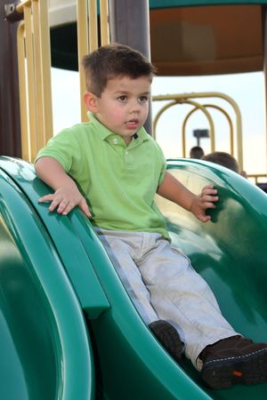 hesitant: Hesitant young boy sitting at the top of a playground sliding board. Stock Photo