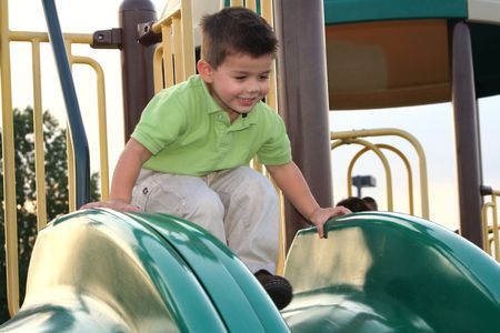 ebullient: Smiling young boy preparing to slide down a playground sliding board.