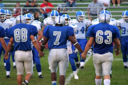 High school football players entering field with linked hands.