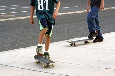Two teenage boys skateboarding.